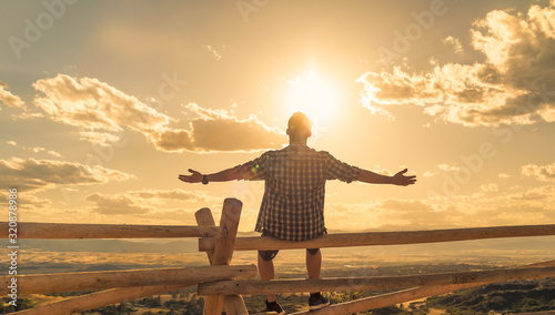 Fotografia Happy man sitting outdoors looking up to the sky with arms outstretched