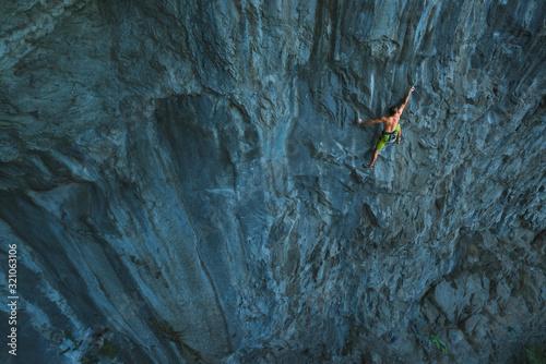 Powerful sportive rock climber climbing Fototapeta