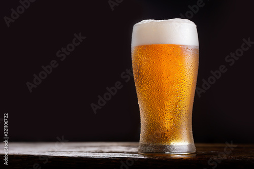 Fototapeta glass of beer on dark background