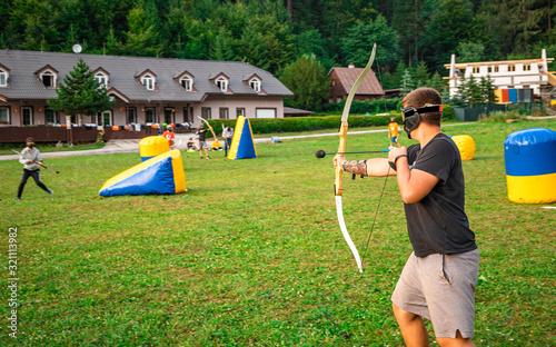 Foto Teenage boy playing archery tag during summer