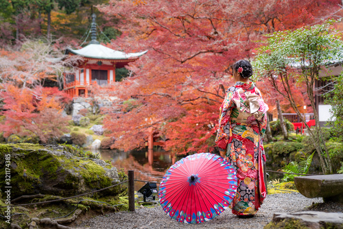 Valokuvatapetti Young Japanese girl traveller in traditional kimino dress standing in Digoji temple with red pagoda and red maple leaf in autumn season in Kyoto, Japan