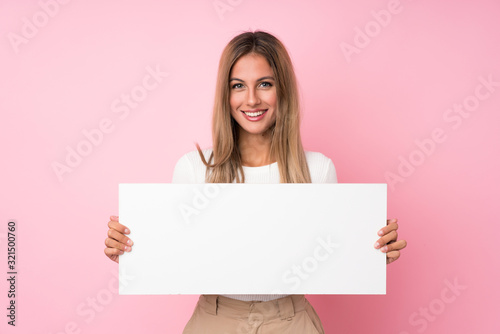Fotografija Young blonde woman over isolated pink background holding an empty white placard