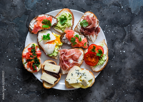 Canvas Print Variety of aperitifs sandwiches plate - sandwiches with prosciutto, avocado, salmon, egg, tomatoes, jamon, gorgonzola, brie, pear on a dark background, top view