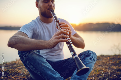 Fotografía Young handsome bearded caucasian blond man sitting on cliff and playing clarinet