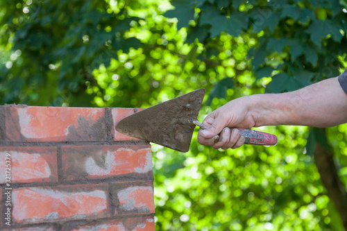 Canvas-taulu Masonry works, male hand working with a trowel, repairing a chimney from red bri