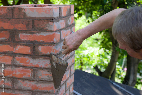 A man making masonry works, working with a trowel and making a chimney of red br Fototapet