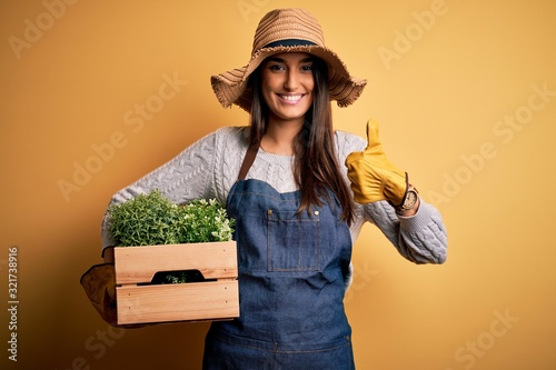 Young beautiful brunette gardener woman wearing apron and hat holding box with p Fototapeta