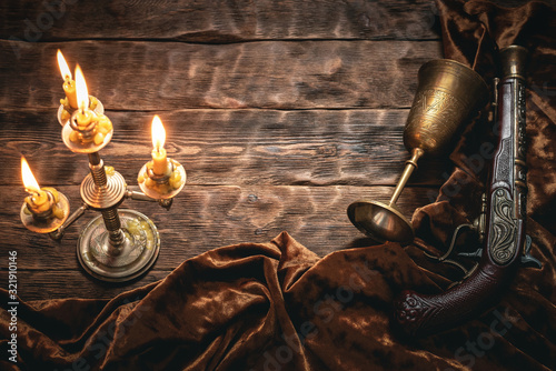 Fotografie, Obraz Old musket gun and golden goblet on pirate desk table in the light of burning candle concept background with copy space
