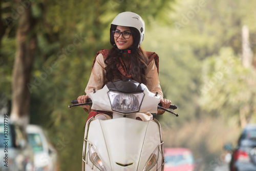 Fotografie, Obraz Smiling young woman wearing eyeglasses and helmet riding scooter looking away
