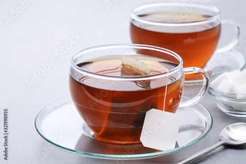 Fototapeta Cup of tea with tea bag on a gray background.