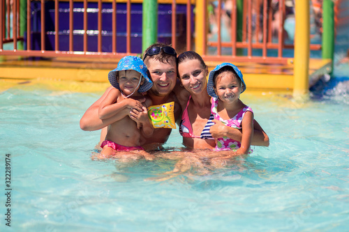Happy European family with two children swimming in the pool of a large beautifu Fototapeta