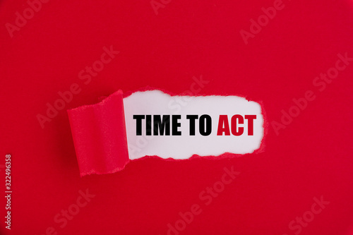 Photo The text Time to act appearing behind torn red paper.
