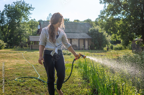 Fotografiet Hipster young woman watering plants a country house, summer and garden care, org