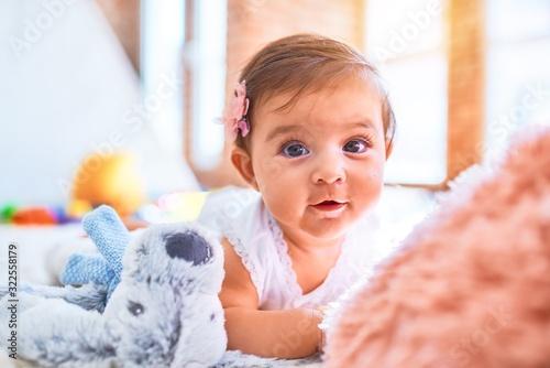 Beautiful infant happy at kindergarten around colorful toys lying on blacket Fototapeta