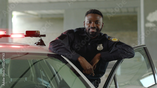 Canvas Print Smiling african american young man cops stand near patrol car look at camera enf