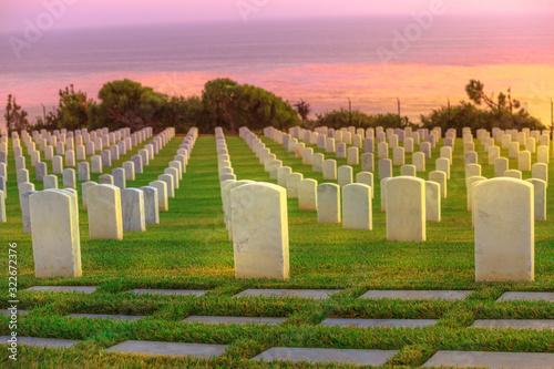 Cemetery graveyard white tombstones at colorful sunset sky Fototapeta