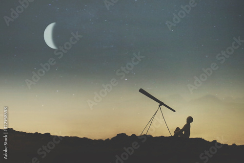 Leinwand Poster silhouette of a boy observing the sky on a starry night with his telescope