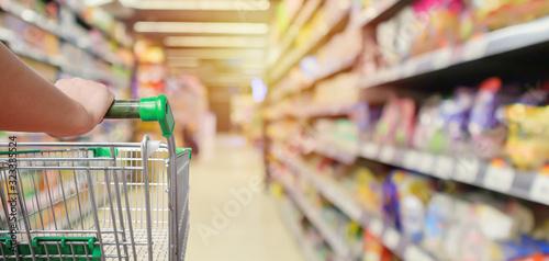 shopping cart in supermarket aisle with product shelves interior defocused blur Fototapet