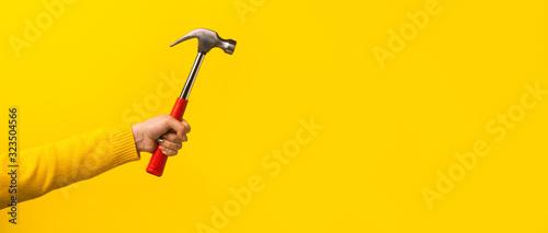Photo Female hand holding hammer on yellow background, panoramic mock-up