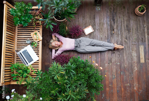 Wallpaper Mural Top view of senior woman with laptop lying outdoors on terrace, resting