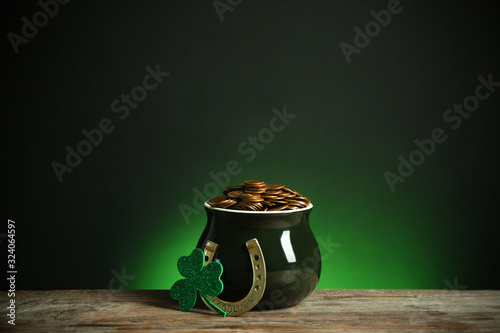 Fotografia Pot with gold coins, horseshoe and clover on wooden table against dark background