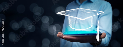 Fotografie, Obraz Man holding tablet with graduation cap on bokeh background