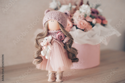 Photo decorative doll in the room on a background of flowers