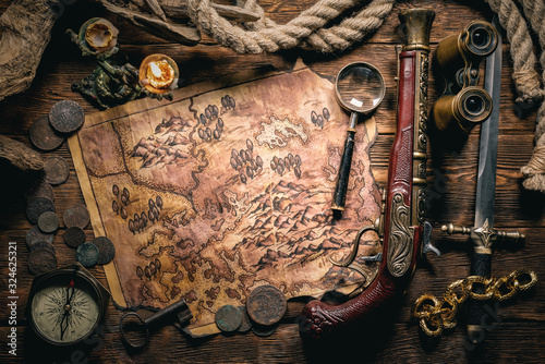 Fotografie, Obraz Pirate treasure map and human skull on brown wooden table closeup background