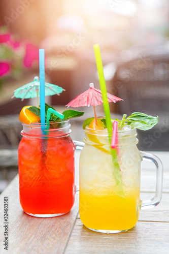 Summer yellow-orange lemonade with ice . Refreshing lemonade with oranges and mint on a wooden table