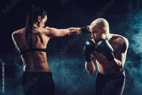 Fotomural Shirtless Woman exercising with trainer at boxing and self defense lesson, studio, dark background