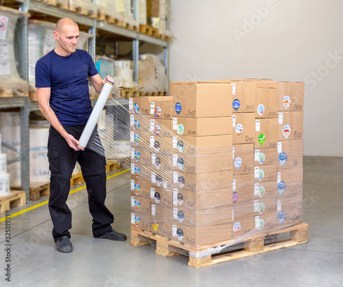 Fotografia Man wrapping (stretching) of a loaded pallet with foil - most common and fastest way to stabilize the goods on the pallet
