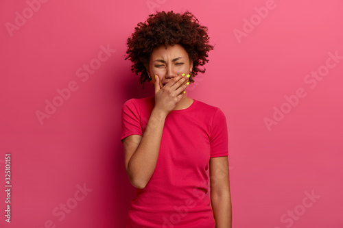 Tableau sur Toile Image of devastated curly Afro American woman feels hurt, cries from despair, expreses sadness, finds out tragic news, sobs upset, feels unwell, regrets something, isolated on pink background