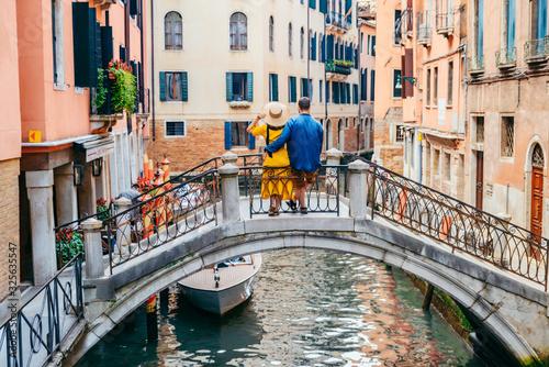 couple standing on the bridge crossing venice canals Fotobehang