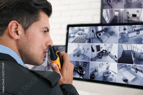 Fotografering Male security guard with portable transmitter near monitors at workplace, closeu