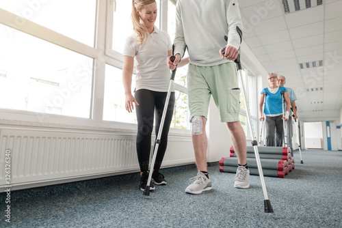 Tela People in rehabilitation learning how to walk with crutches