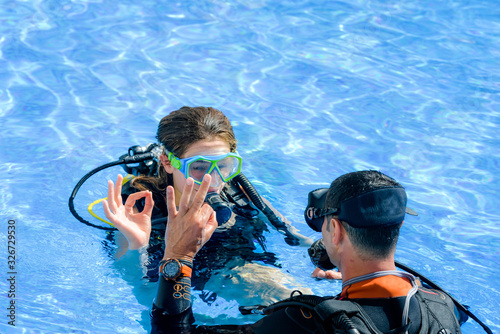 Fotografie, Obraz beautiful young woman taking a scuba diving lesson in swimming pool