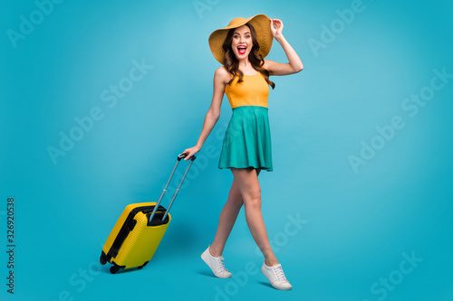 Full size profile photo of pretty lady traveler rolling suitcase walking airport flight check-in good mood resort tour wear mini summer dress hat shoes isolated blue background