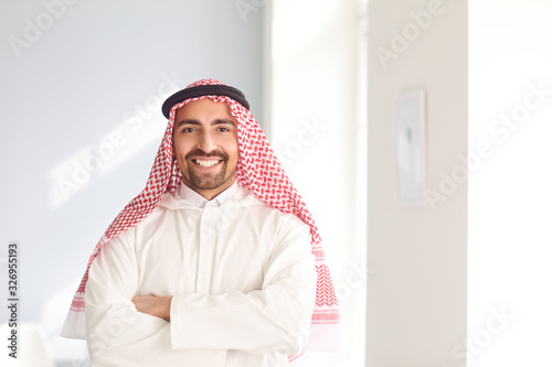 Positive arabic man smiling while standing in a white bright room Fototapeta
