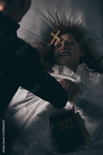 Valokuvatapetti exorcist with bible and cross standing over demoniacal girl in bed