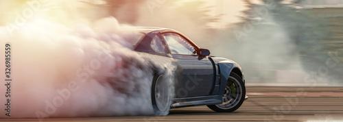 Samochód dryfujący, rozmyty obraz wyścigowy samochód dryfujący z dużą ilością dymu z płonących opon na torze prędkości.