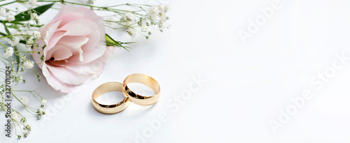 Valokuva Pink flowers and two golden wedding rings on white background.