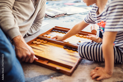 Fototapeta Dad and little son play backgammon - friendly family - leisure with a child