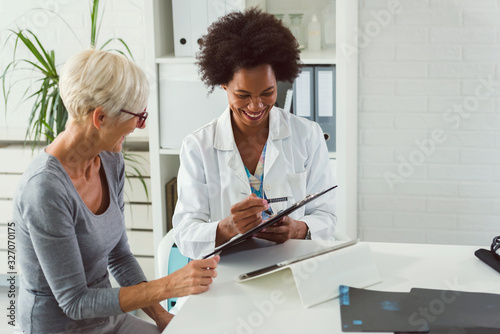 Fotografie, Obraz A female doctor sits at her desk and chats to an elderly female patient while lo