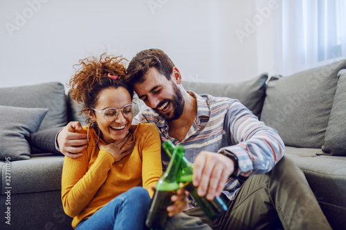 Fotografía Young happy attractive caucasian couple sitting on the floor in living room and toasting with beer