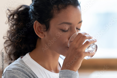 Fotografía Thirsty african American woman drinking mineral water