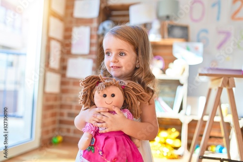 Wallpaper Mural Adorable blonde toddler hugigng doll around lots of toys at kindergarten