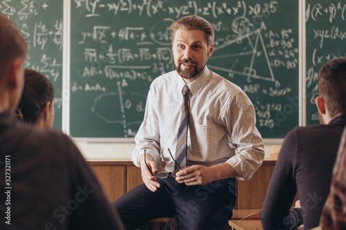Obraz na płótnie Cheerful bearded professor having a casual informal conversation with students d
