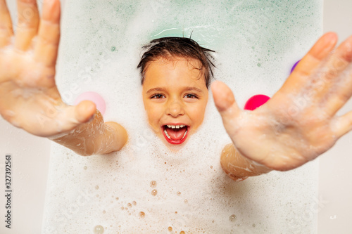 Valokuvatapetti Cute boy with smile laugh and happy scream swim on the back in soap at home bath