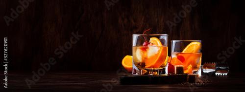 Fotografia Alcoholic old fashioned cocktail with orange slice, cherry and orange peel garni