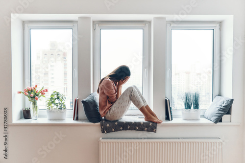 Sad young woman crying about something while sitting on the window sill at home Fototapeta